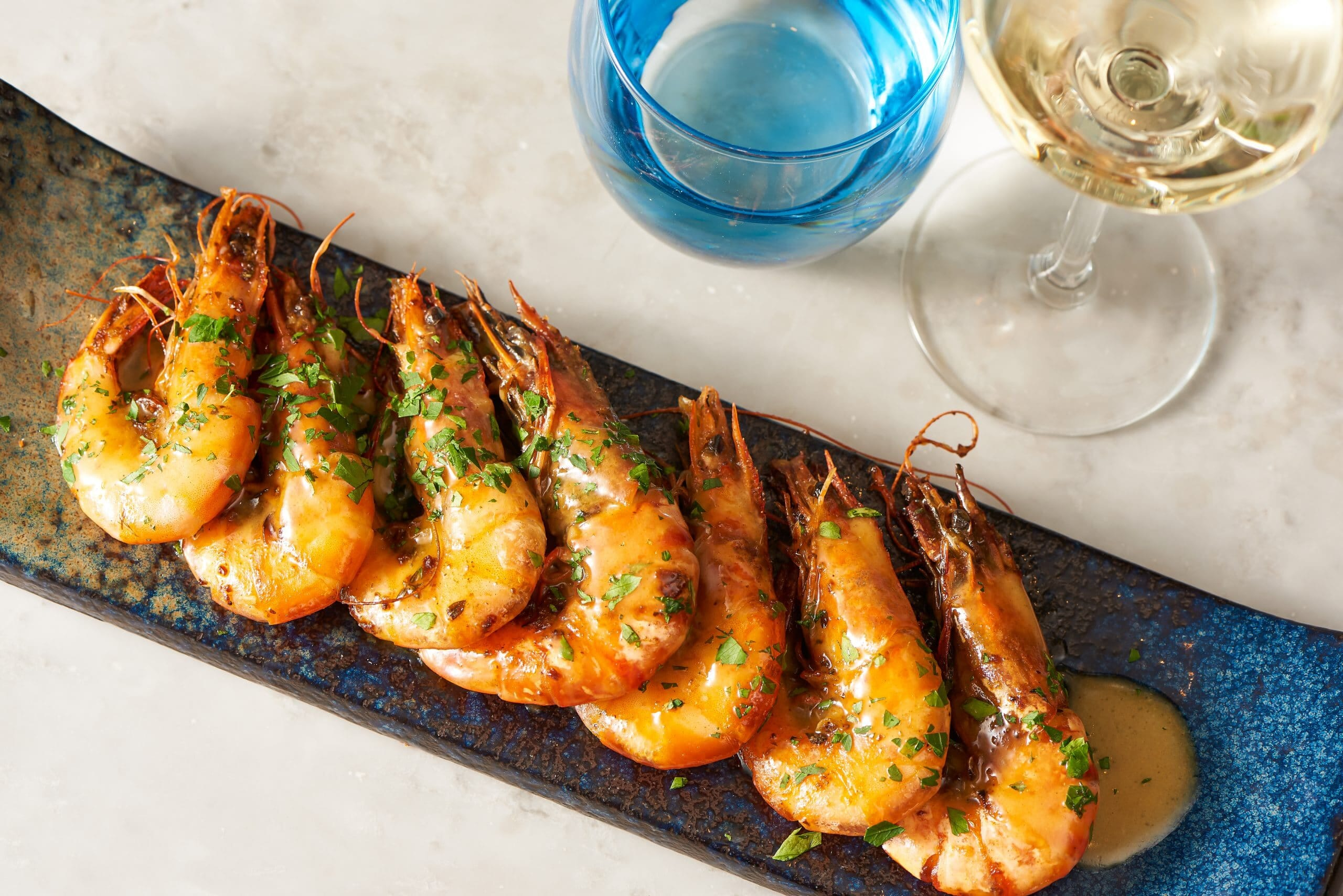 Grilled king prawns and white wine restaurant food photography London
