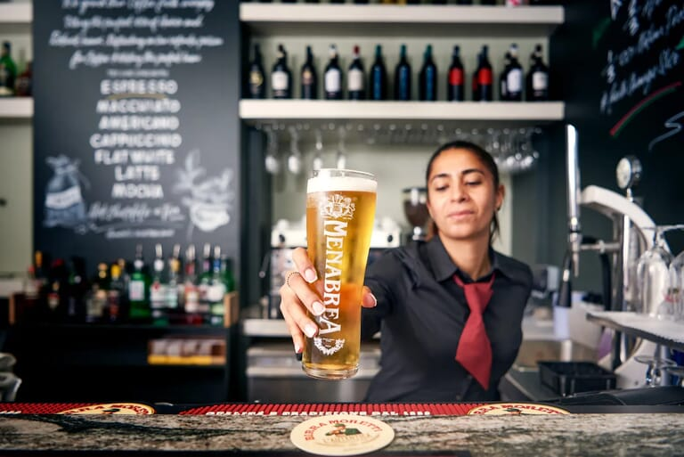 Barista serving a pint of menabrea beer in London, commercial lifestyle photograhy